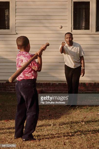 Martin Luther King Jr throws a baseball to his son Marty in their backyard