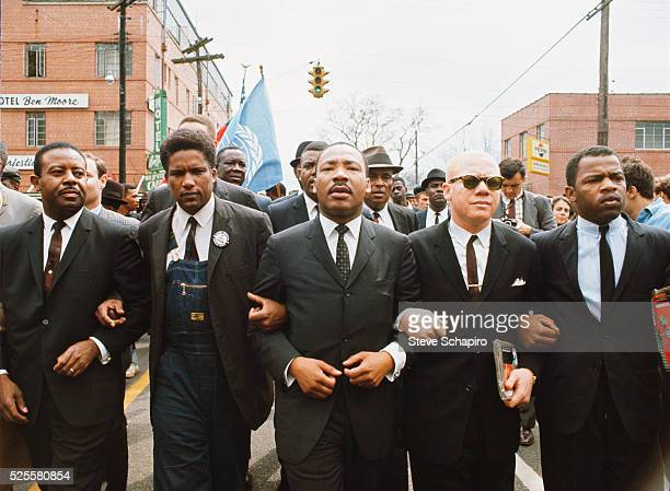 Martin Luther King leading a march from Selma to Montgomery to protest the lack of voting rights for African Americans Beside King is John Lewis the...