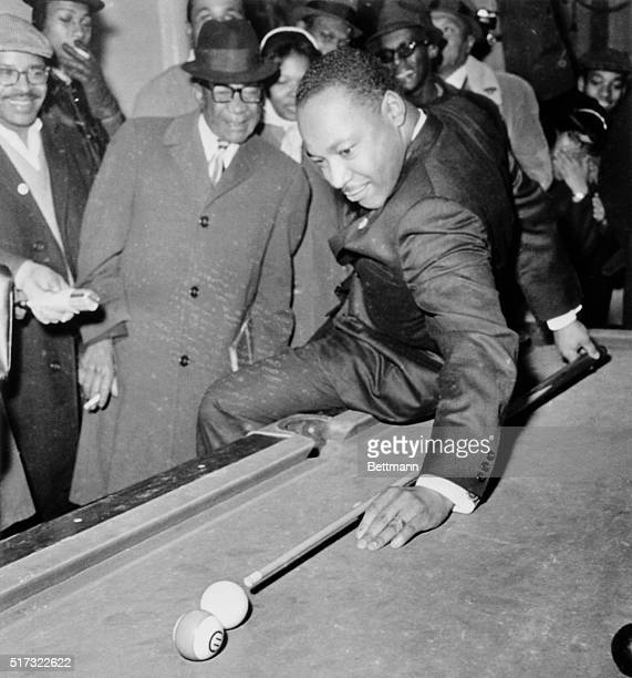 Martin Luther King tries difficult behind the back shot while using his 'best stick' in pool match with Chicago civil rights leader Al Raby while on...