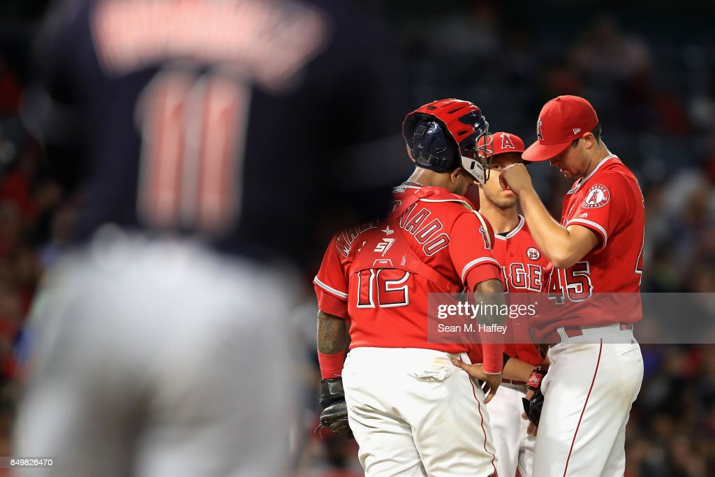 Martin Maldonado #12 and Andrelton Simmons #2 talk with Tyler Skaggs #45 of the Los Angeles Angels of Anaheim during the fifth inning of a game against the Cleveland Indians at Angel Stadium of Anaheim on September 19, 2017 in Anaheim, California.