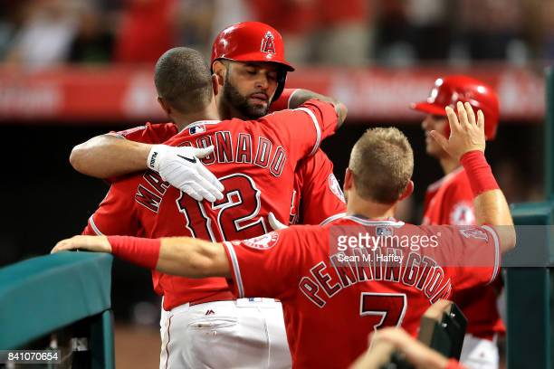 Martin Maldonado and Cliff Pennington congratulate Albert Pujols of the Los Angeles Angels after his tworun homerun during the fifth inning of a game...