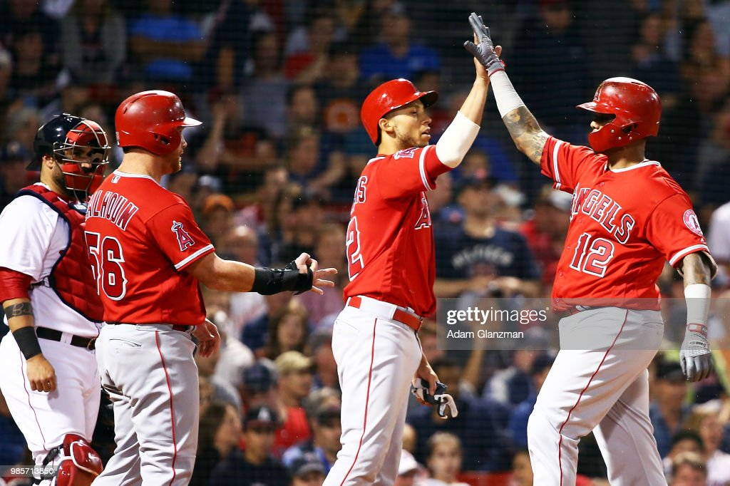 Martin Maldonado #12 high fives Andrelton Simmons #2 of the Los Angeles Angels after hitting a three run home run in the sixth inning of a game against the Boston Red Sox at Fenway Park on June 27, 2018 in Boston, Massachusetts.
