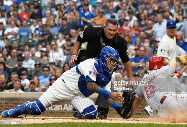 Martin Maldonado of the Chicago Cubs tags out Nick Senzel of the Cincinnati Reds at home plate during the first inning at Wrigley Field on July 16...