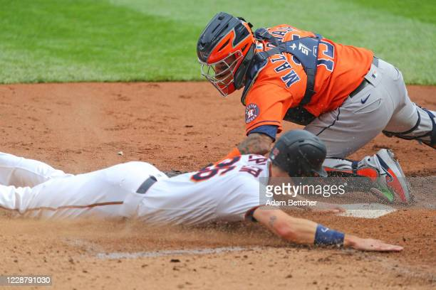 Martin Maldonado of the Houston Astros unsuccessfully attempts the tag on Max Kepler of the Minnesota Twins allowing the first run of the game in the...