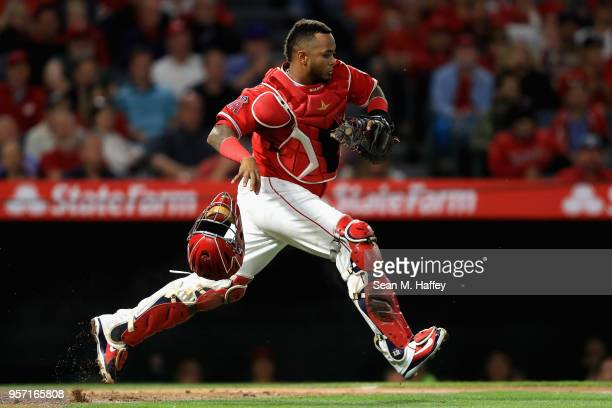 Martin Maldonado of the Los Angeles Angels of Anaheim chases a pass ball during the sixth inning of a game against the Minnesota Twins at Angel...