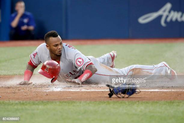 Martin Maldonado of the Los Angeles Angels of Anaheim slides across home plate to score a run in the fourth inning during MLB game action against the...
