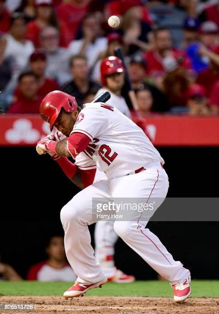 Martin Maldonado of the Los Angeles Angels reacts as he is hit on the helmet by a pitch during the second inning against the Oakland Athletics at...