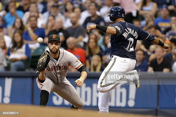 Martin Maldonado of the Milwaukee Brewers beats the throw to Brandon Belt of the San Francisco Giants at first base during the bottom of the second...