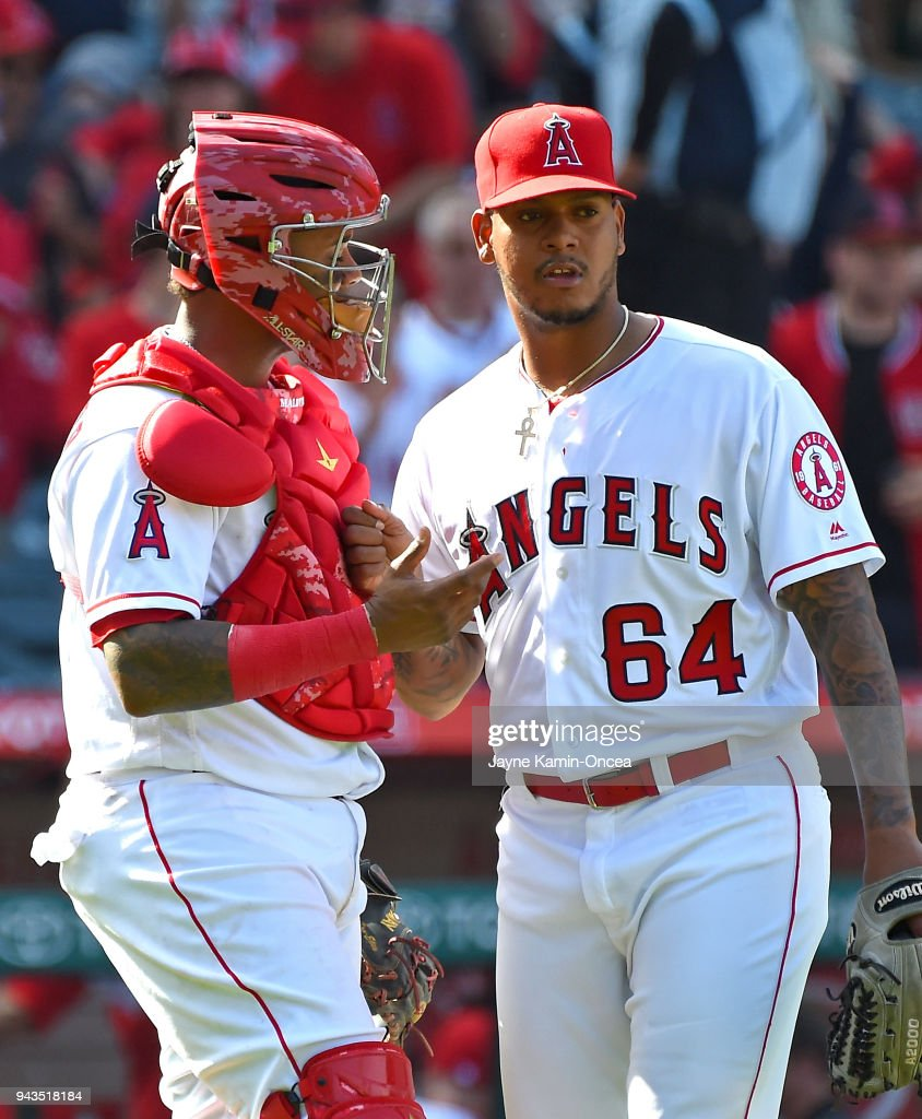 Martin Maldonado #12 shakess hands with Felix Pena #64 of the Los Angeles Angels after defeating the Oakland Athletics at Angel Stadium of Anaheim on April 8, 2018 in Anaheim, California.