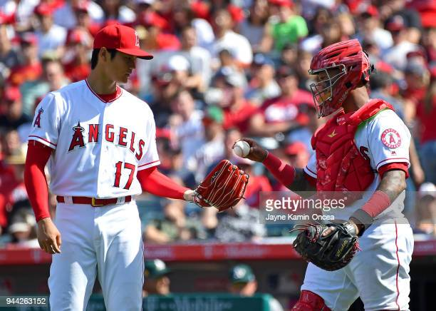 Martin Maldonado walks to the mound to talk with Shohei Ohtani of the Los Angeles Angels in the seventh inning of the game against the Oakland...