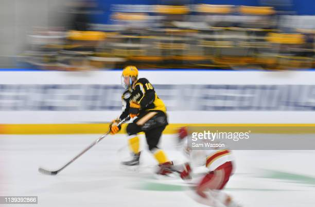 Martin Mellberg of the American International Yellow Jackets skates with the puck ahead of Ryan Barrow of the Denver Pioneers during the NCAA...