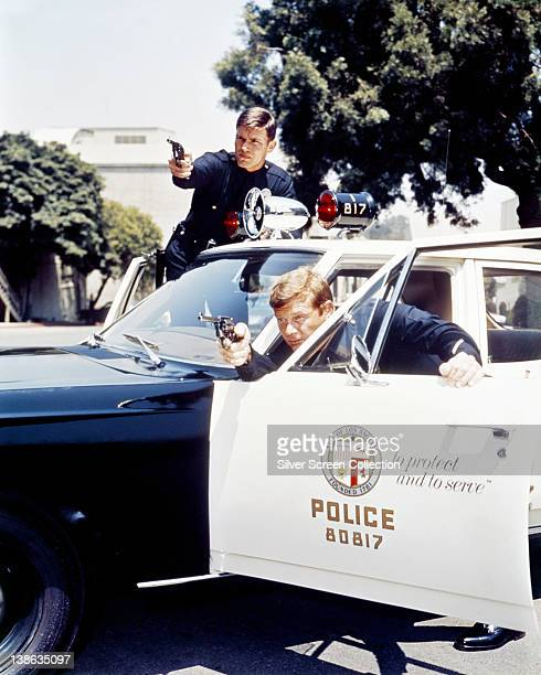 Martin Milner US actor and Kent McCord US actor both in costume as LAPD police officers pointing handguns as they shield beside their police car in...