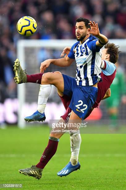 Martin Montoya of Brighton Hove Albion and Mark Noble of West Ham United clash during the Premier League match between West Ham United and Brighton...