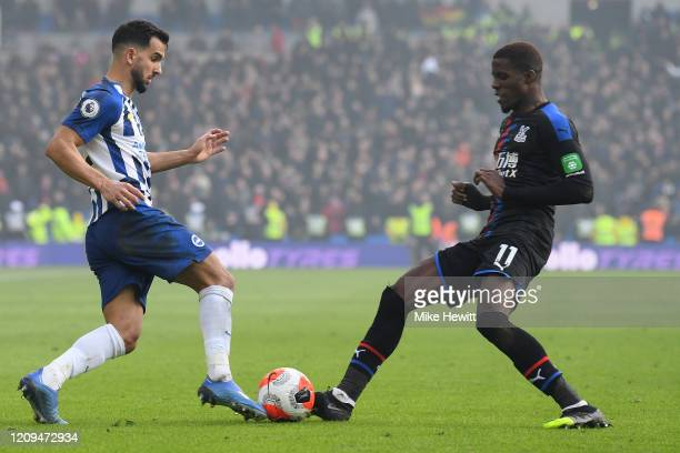 Martin Montoya of Brighton Hove Albion is challenged by Wilfried Zaha of Crystal Palace during the Premier League match between Brighton Hove Albion...