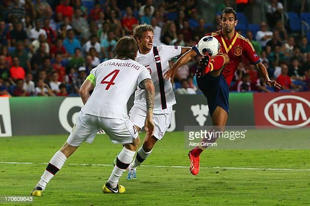 Martin Montoya of Spain is challenged by Vegar Eggen Hedenstad and Stefan Strandberg of Norway during the UEFA European U21 Championship Semi Final...