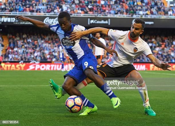 Martin Montoya of Valencia competes for the ball with Marlos Moreno of Deportivo de La Coruna during the La Liga match between Valencia CF and...