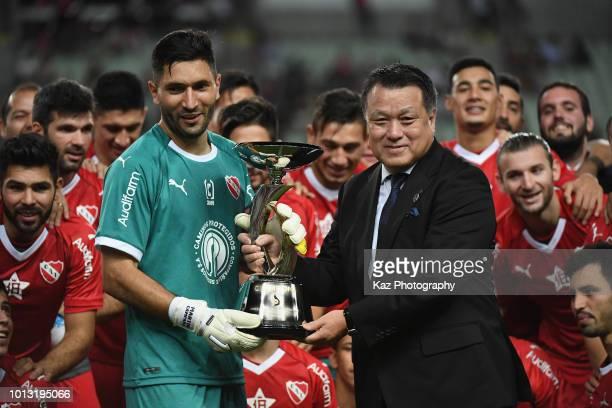 Martin Nicolas Campana Delgado of Independiente receives the trophy from the Japan Football Association President Kozo Tashima after the Suruga Bank...