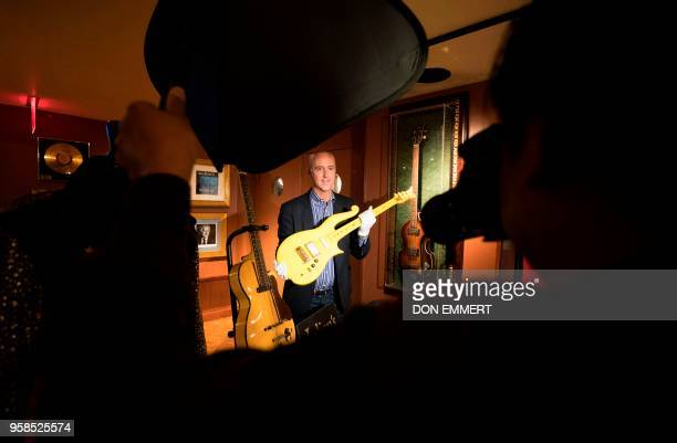 Martin Nolan Executive Director of Julien's Auctions holds Prince's stage played Yellow Cloud guitar during a media preview May 14 2018 in New York...