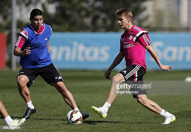 Martin Odegaard and James Rodriguez of Real Madrid in action during a training session at Valdebebas training ground on April 2 2015 in Madrid Spain