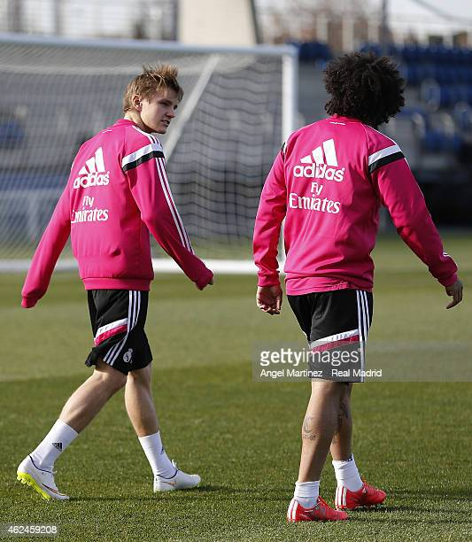Martin Odegaard and Marcelo Vieira of Real Madrid chat during a training session at Valdebebas training ground on January 29 2015 in Madrid Spain