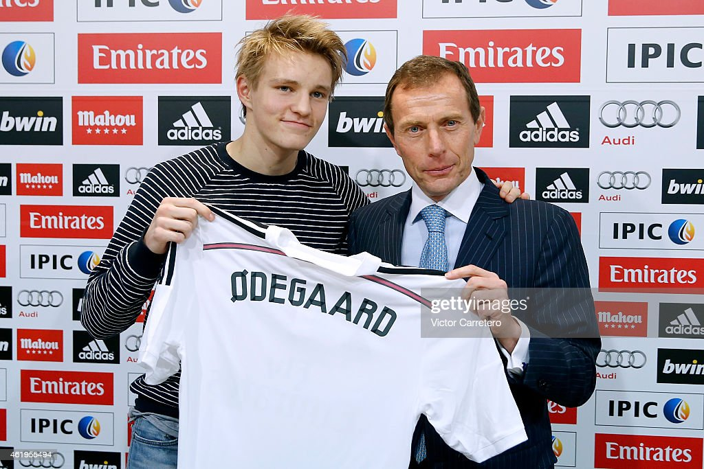 Martin Odegaard (L) from Norway holds his new Real Madrid shirt with former Real Madrid player Emilio Butragueno during his official presentation at the Valdebebas Ciudad Real Madrid in Madrid on January 22, 2015 in Madrid, Spain.