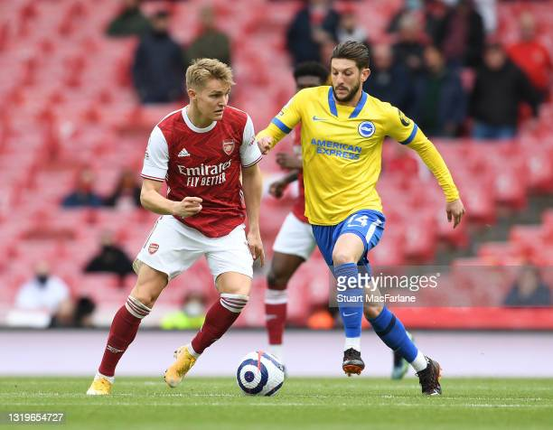 Martin Odegaard of Arsenal breaks past Adam Lallana of Brighton during the Premier League match between Arsenal and Brighton & Hove Albion at...