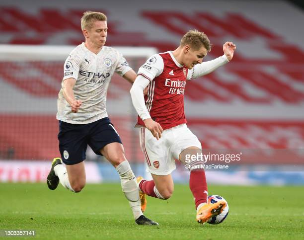 Martin Odegaard of Arsenal breaks past Oleksandr Zinchenko of Man City during the Premier League match between Arsenal and Manchester City at...