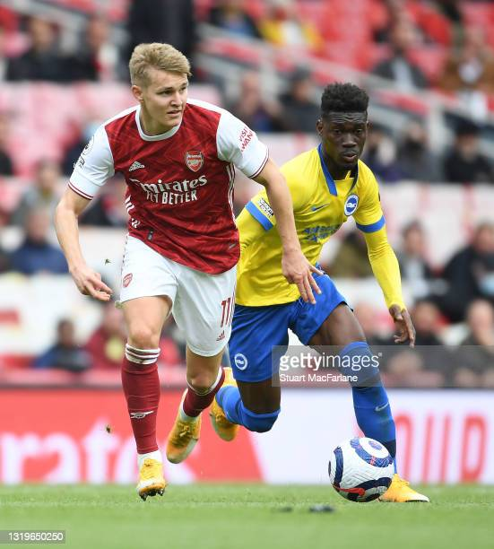 Martin Odegaard of Arsenal breaks past Yves Bissouma of Brighton during the Premier League match between Arsenal and Brighton & Hove Albion at...