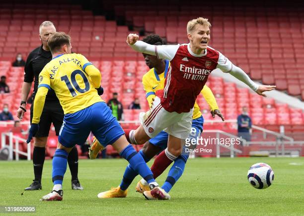 Martin Odegaard of Arsenal is challenged by Alexis Mac Allister and Yves Bissouma of Brighton during the Premier League match between Arsenal and...