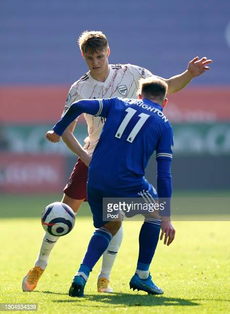 Martin Odegaard of Arsenal is challenged by Marc Albrighton of Leicester City during the Premier League match between Leicester City and Arsenal at...