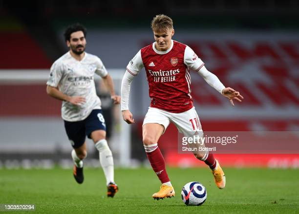 Martin Odegaard of Arsenal runs with the ball during the Premier League match between Arsenal and Manchester City at Emirates Stadium on February 21,...