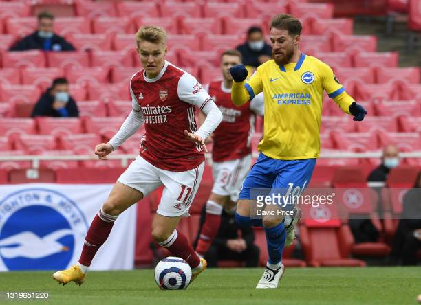 Martin Odegaard of Arsenal takes on Alexis Mac Allister of Brighton during the Premier League match between Arsenal and Brighton & Hove Albion at...