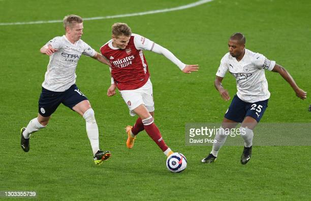 Martin Odegaard of Arsenal takes on Oleksandr Zinchenko and Fernandinho of Man City during the Premier League match between Arsenal and Manchester...