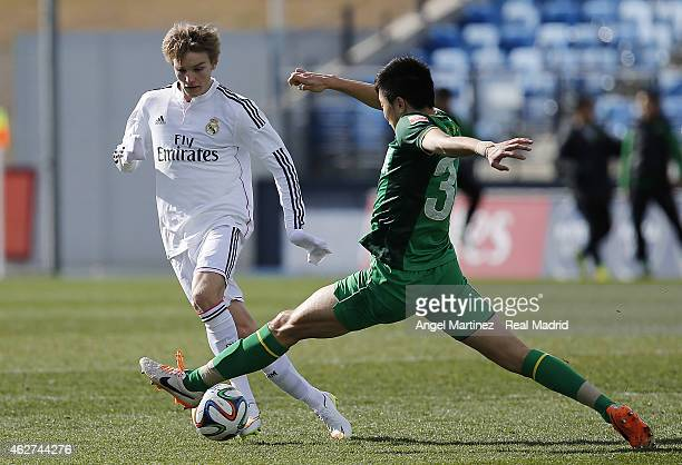 Martin Odegaard of Real Madrid Castilla competes for the ball with Li Lei of Beijing Guoan during a friendly match between Real Madrid Castilla and...
