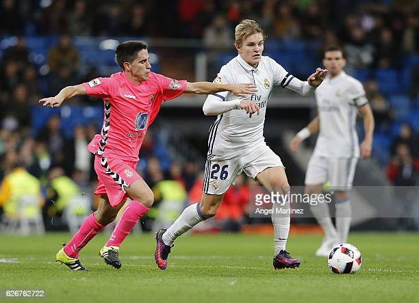 Martin Odegaard of Real Madrid competes for the ball with Cristobal Gil of Cultural y Deportiva Leonesa during the Copa del Rey round of 32 second...