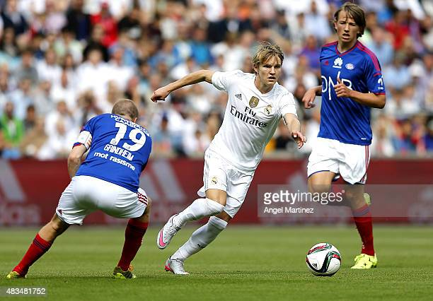 Martin Odegaard of Real Madrid is chased by Christian Grindheim and Sander Berge of Valerenga during the preseason friendly match between Valerenga...