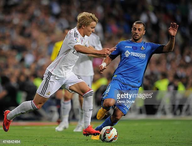 Martin Odegaard of Real Madridis tackled by Medhi Lacen of Getafe CF during the La Liga match between Real Madrid CF and Getafe CF at Estadio...