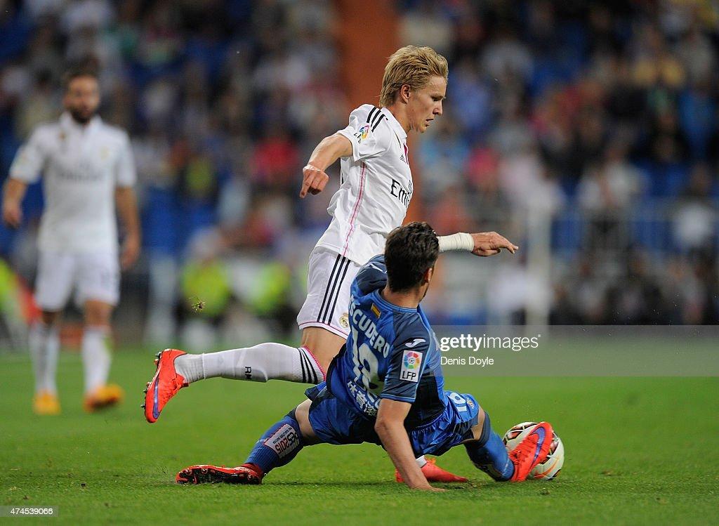 Martin Odegaard of Real Madridis tackled by Sergio Escudero of Getafe CF during the La Liga match between Real Madrid CF and Getafe CF at Estadio Santiago Bernabeu on May 23, 2015 in Madrid, Spain.