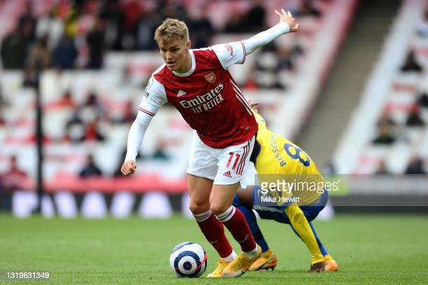 Martin Oedegaard of Arsenal is put under pressure by Yves Bissouma of Brighton & Hove Albion during the Premier League match between Arsenal and...