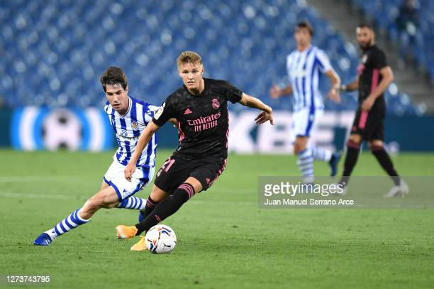 Martin Oedegaard of Real Madrid battles for possession with Aritz Elustondo of Real Sociedad during the La Liga Santander match between Real Sociedad...