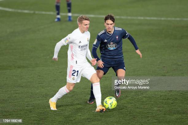 Martin Oedegaard of Real Madrid battles for possession with Denis Suarez of Celta Vigo during the La Liga Santander match between Real Madrid and RC...