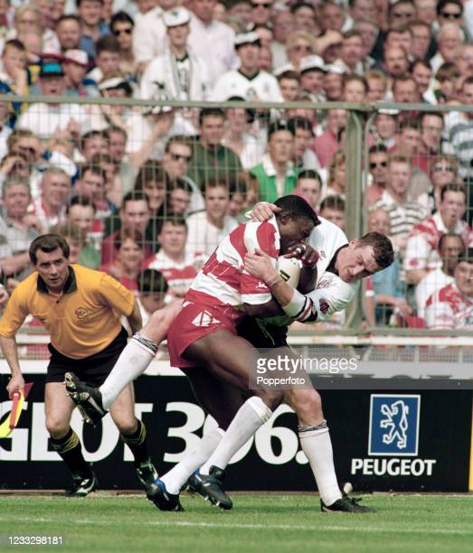 Martin Offiah of Wigan is tackled by Andy Currier of Widnes during the Silk Cut Challenge Cup Final at Wembley Stadium on May 1, 1993 in London,...