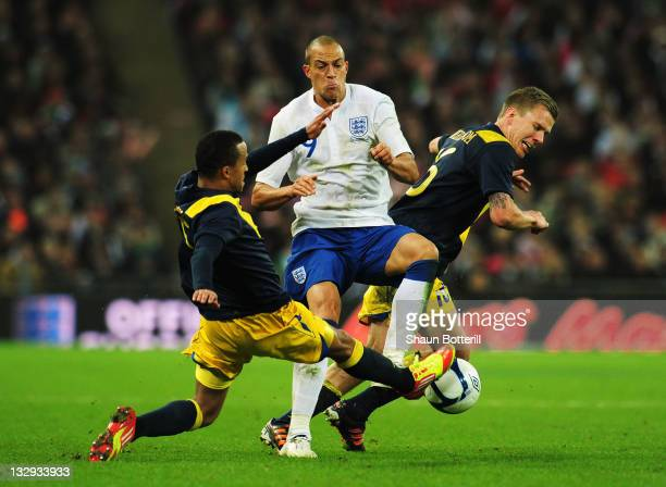 Martin Olsson and Pontus Wernbloom of Sweden challenge Bobby Zamora of England during the international friendly match between England and Sweden at...