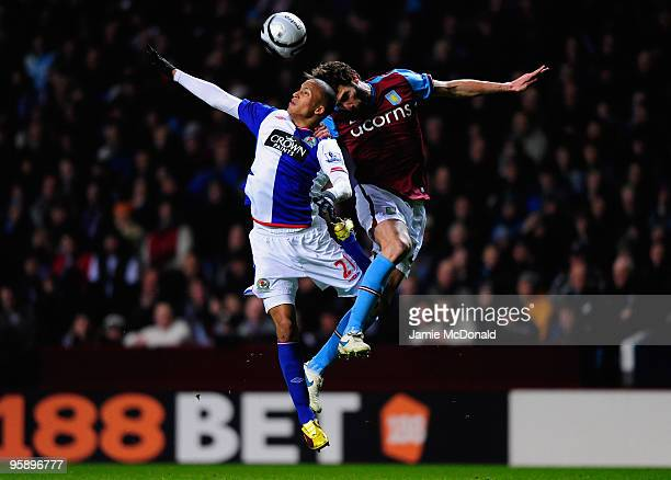 Martin Olsson of Blackburn Rovers jumps for a header with Carlos Cuellar of Aston Villa during the Carling Cup SemiFinal second leg match between...