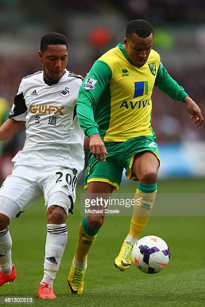 Martin Olsson of Norwich City shields the ball from Jonathan de Guzman of Swansea City during the Barclays Premier League match between Swansea City...