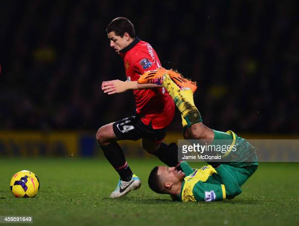 Martin Olsson of Norwich City tangles with Javier Hernandez of Manchester United during the Barclays Premier League match between Norwich City and...
