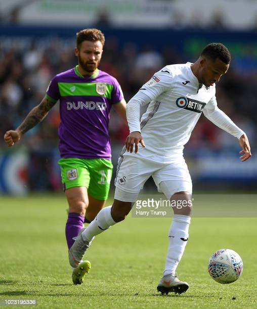 Martin Olsson of Swansea City looks to break past Matty Taylor of Bristol City during the Sky Bet Championship match between Swansea City and Bristol...