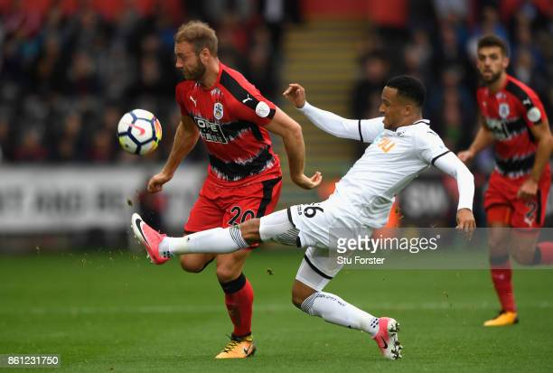 Martin Olsson of Swansea City tackles Laurent Depoitre of Huddersfield Town during the Premier League match between Swansea City and Huddersfield...