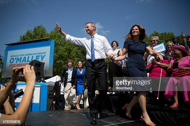 Martin O'Malley, former governor of Maryland, left, waves as he arrives with his wife Katie O'Malley to announce he will seek the Democratic...