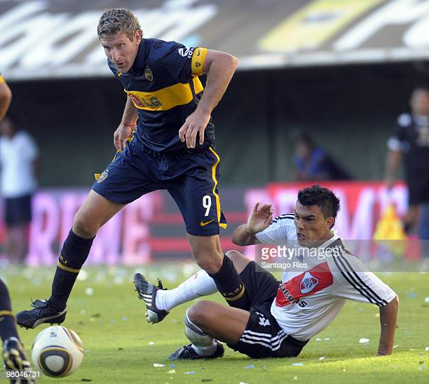 Martin Palermo of Boca Juniors vies for the ball with Gustavo Cabral of River Plate during a match as part of the Clausura 2010 on March 25 2010 in...